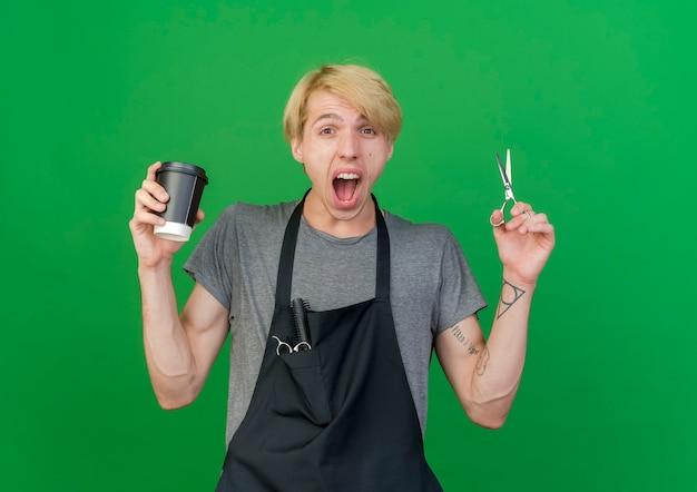 Homme de coiffeur professionnel en tablier tenant une tasse de café et des ciseaux criant d'être excité