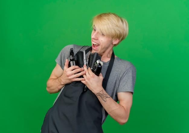 Homme de coiffeur professionnel en tablier tenant une tondeuse et des brosses à cheveux à côté souriant joyeusement