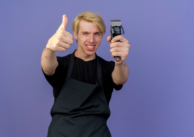 Homme de coiffeur professionnel en tablier tenant tondeuse heureux et joyeux montrant les pouces vers le haut debout sur le mur bleu