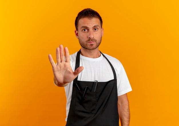 Homme de coiffeur en tablier faisant panneau d'arrêt avec la main à l'avant avec un visage sérieux debout sur un mur orange