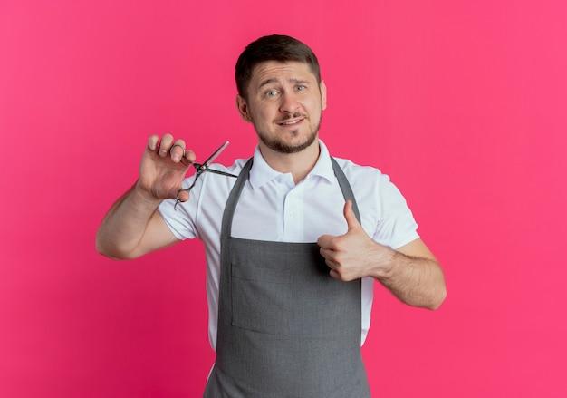 Homme de coiffeur en tablier montrant des ciseaux montrant les pouces vers le haut debout sur fond rose