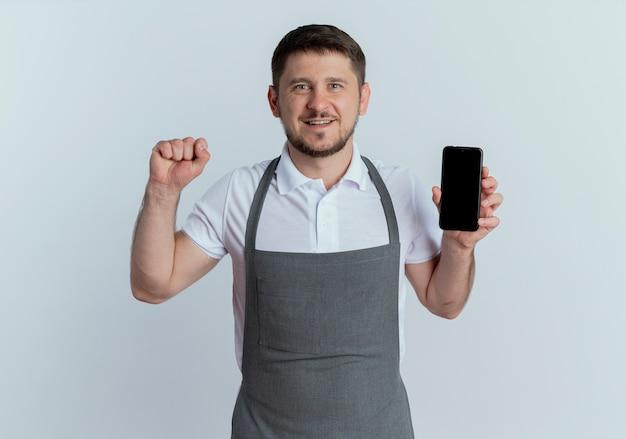 Homme de coiffeur en tablier montrant smartphone levant le poing heureux et positif regardant la caméra debout sur fond blanc