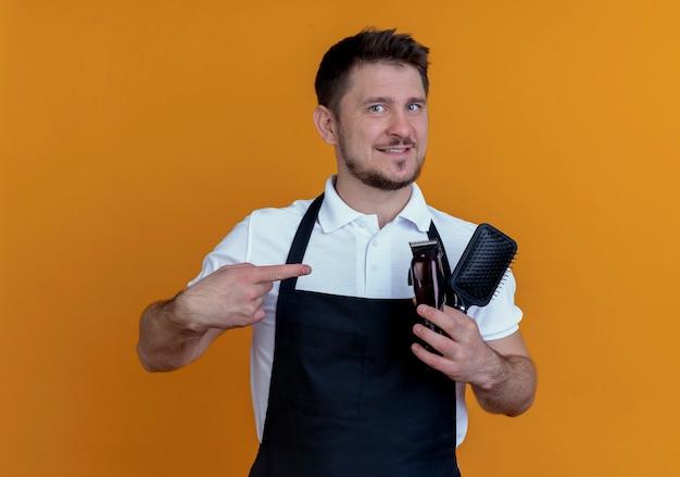Homme de coiffeur en tablier tenant une brosse à cheveux et une tondeuse à barbe pointant avec le doigt sur eux sourire confiant debout sur fond orange