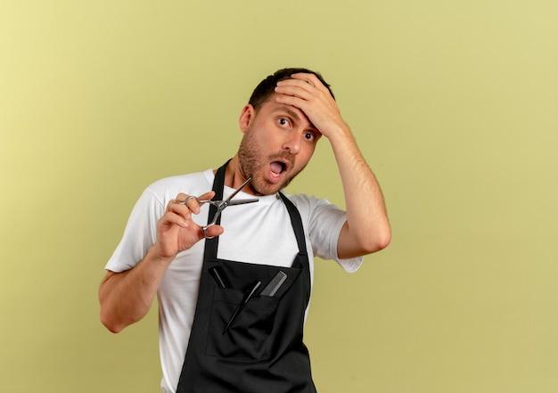 Homme de coiffeur en tablier tenant des ciseaux à l'avant choqué avec la main sur la tête debout sur un mur léger