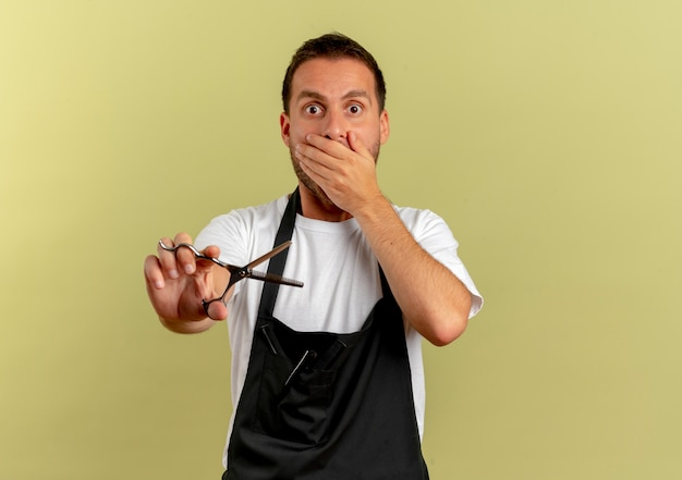 Homme de coiffeur en tablier tenant des ciseaux choqué couvrant la bouche avec la main debout sur un mur léger