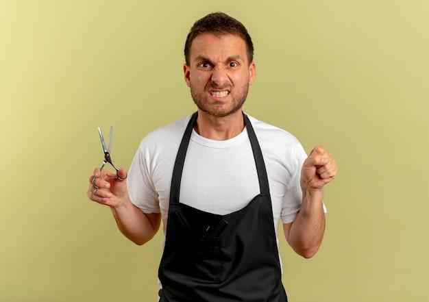 Homme de coiffeur en tablier tenant des ciseaux serrant le poing à l'avant avec visage en colère debout sur un mur léger