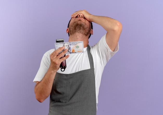 Homme de coiffeur en tablier tenant la machine de coupe de cheveux dérangé couvrant les yeux avec la main debout sur le mur violet