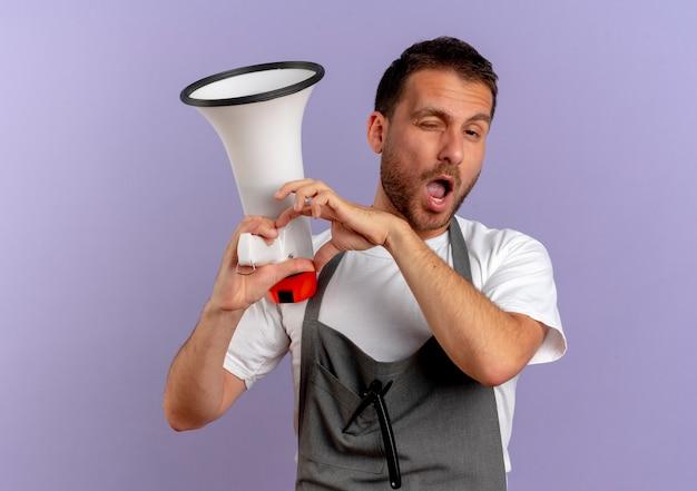 Homme de coiffeur en tablier tenant un mégaphone à l'avant en souriant et en clignant des yeux faisant le geste du cœur avec les doigts sur la poitrine debout sur le mur violet