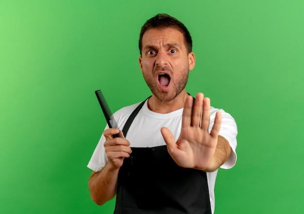 Homme de coiffeur en tablier tenant un peigne faisant panneau d'arrêt avec la main en criant debout sur un mur vert
