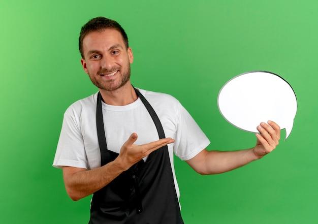 Homme de coiffeur en tablier tenant un signe de bulle de discours vierge le présentant avec le bras de sa main debout sur le mur vert