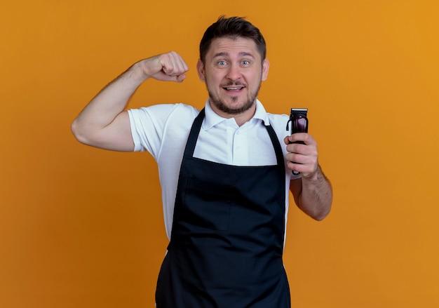 Homme de coiffeur en tablier tenant tondeuse à barbe levant le poing regardant la caméra en souriant joyeusement debout sur fond orange