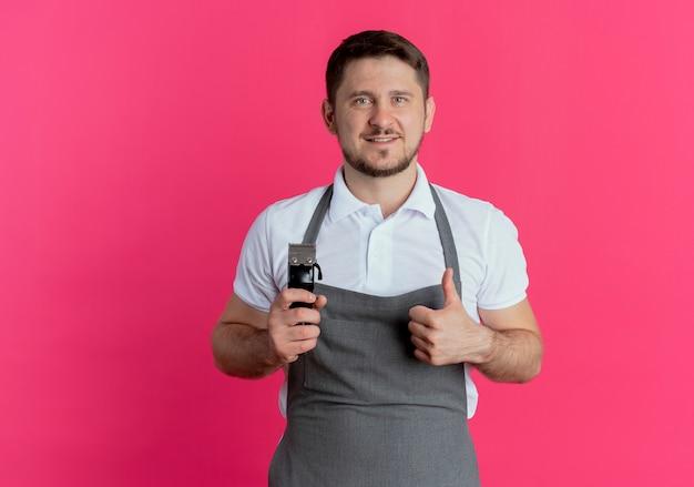 Homme de coiffeur en tablier tenant tondeuse à barbe montrant les pouces vers le haut en souriant regardant la caméra debout sur fond rose