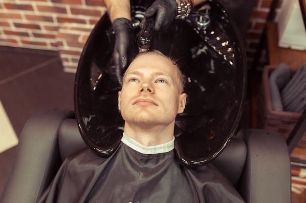 L'homme de coiffure lave la tête du client dans le salon de coiffure vintage