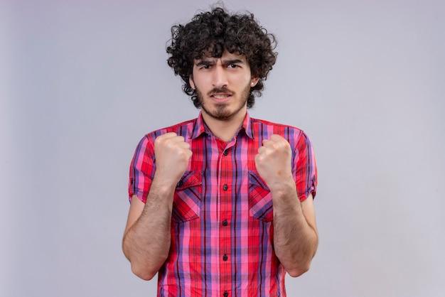 Un homme en colère et agressif aux cheveux bouclés en chemise à carreaux montrant les poings fermés avec les doigts
