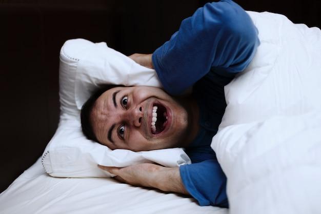 Homme en colère à l'aide d'un oreiller pour couvrir ses oreilles