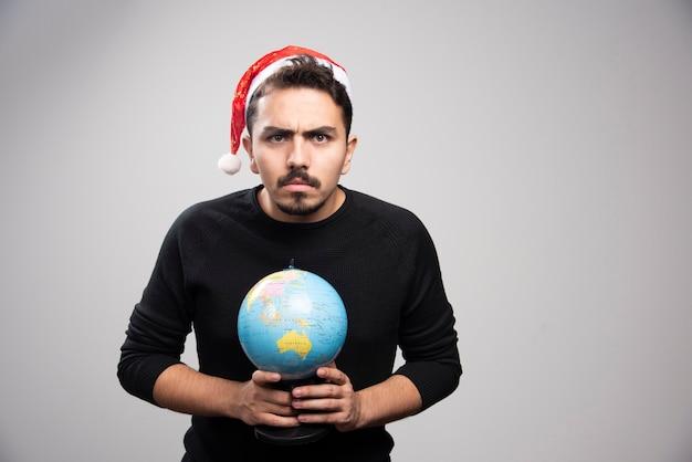Homme en colère au chapeau du père noël tenant un globe.