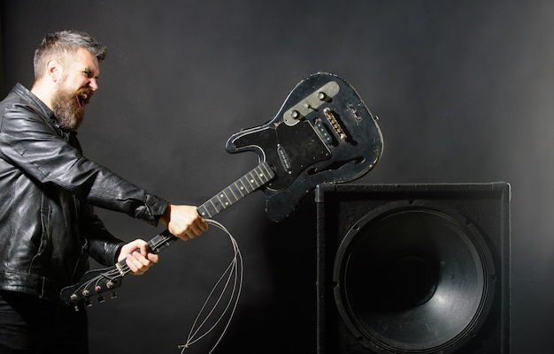 Un homme en colère avec de la barbe casse la guitare à des haut-parleurs de musique émotions agression instruments de musique guitare
