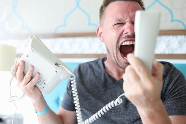 Homme en colère criant dans le téléphone dans la chambre d'hôtel