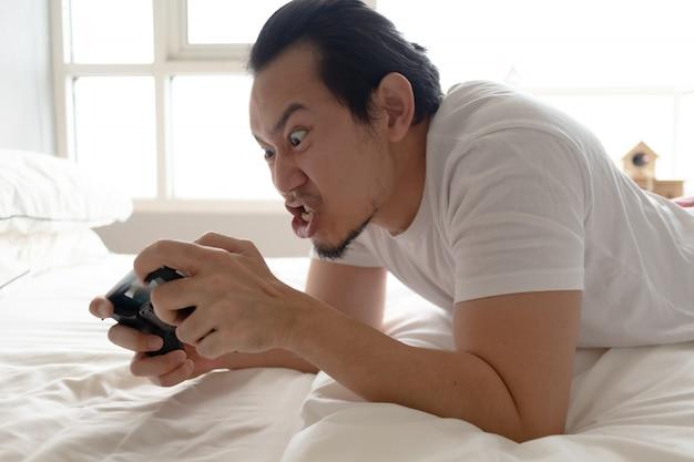 Un homme en colère et furieux est accro au jeu mobile.