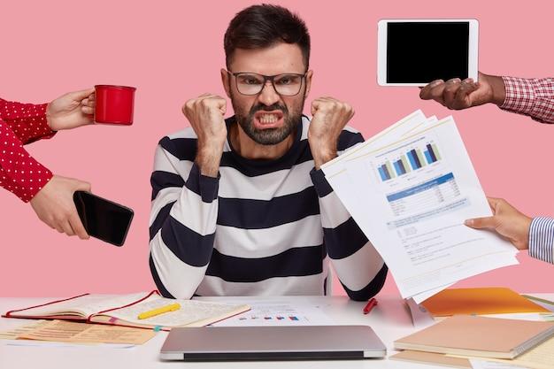 Un homme en colère indigné a un chaume épais, serre les poings de colère, des personnes méconnaissables lui tendent la main avec des papiers, un téléphone portable, un bloc-notes et une tasse