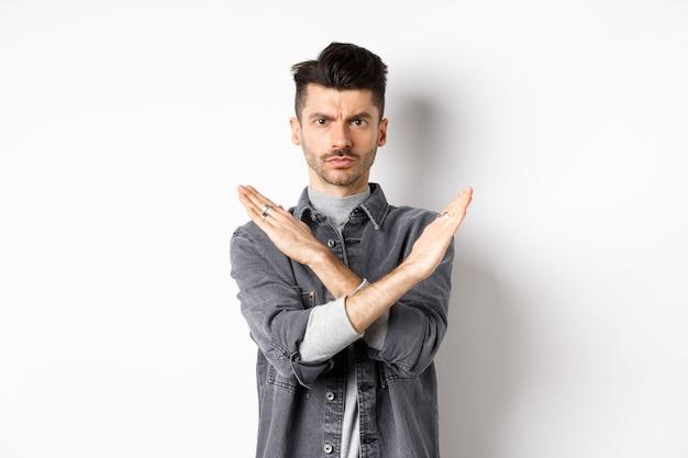 Homme en colère montre un geste croisé pour arrêter ou dire non, froncer les sourcils et regarder sérieux, en désaccord et interdire une mauvaise situation, debout sur fond blanc.