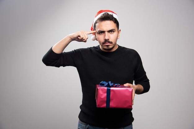 Homme en colère tenant une boîte-cadeau sur un mur gris.