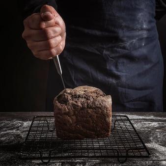 Homme collant un couteau dans le pain