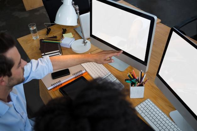 Homme et collègue discutant sur pc de bureau