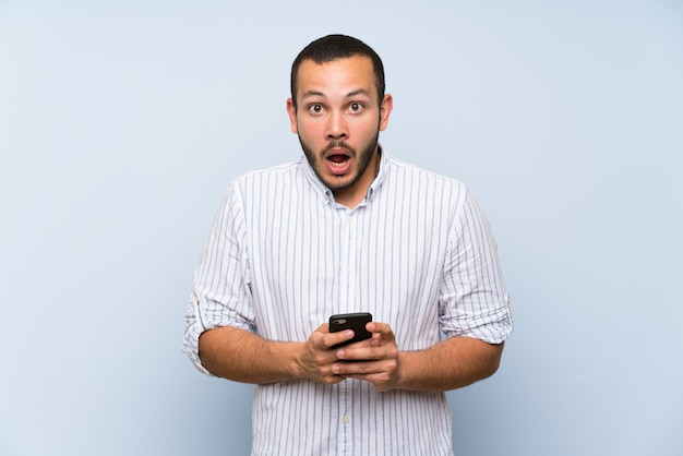 Homme colombien sur mur bleu isolé surpris et envoyant un message