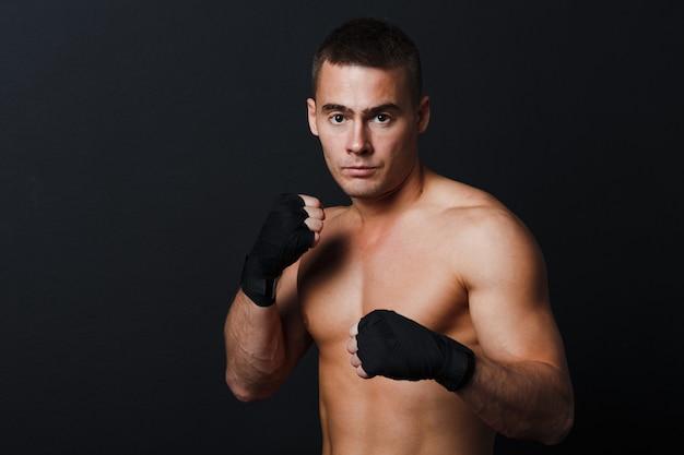 Homme combattant aux articulations nues au mur noir avec des bandages de boxe
