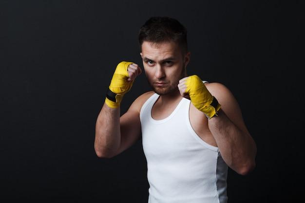 Homme combattant aux articulations nues au mur noir