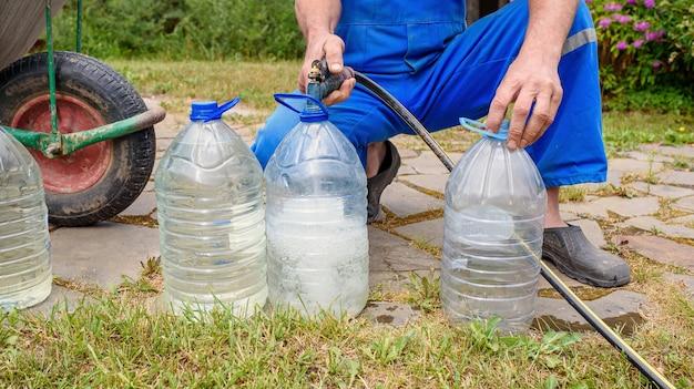 Un homme en combinaison bleue verse de l'eau potable d'un tuyau dans de grandes bouteilles. eau potable écologique provenant d'un puits dans une maison de campagne.