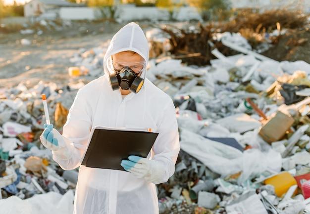 Homme en combinaison à la poubelle. fais des recherches. concept d'écologie, pollution de l'environnement.