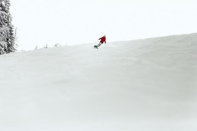 Homme en combinaison de ski rouge exécute un tour de talon