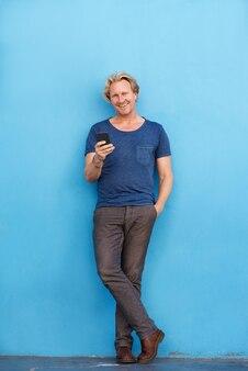 Homme complet, debout, mur, téléphone portable