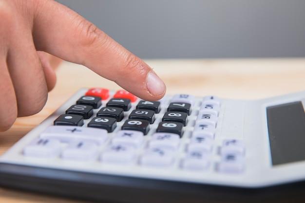 Un homme comptant sur une calculatrice