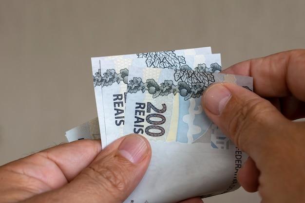 Homme comptant les factures d'argent brésilien