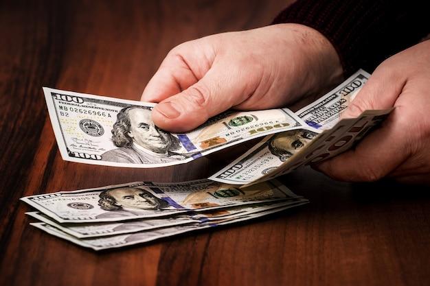 Un homme compte de l'argent. paiement à l'achat_