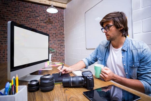 Homme concentré à l'aide d'ordinateur au bureau
