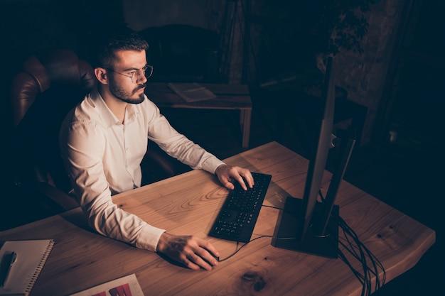 Homme concentré au bureau de nuit assis sur la table de travail pc