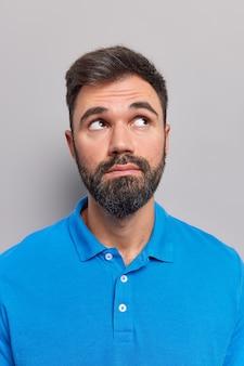 L'homme concentré au-dessus considère que quelque chose a les cheveux noirs porte un t-shirt bleu décontracté isolé sur gris
