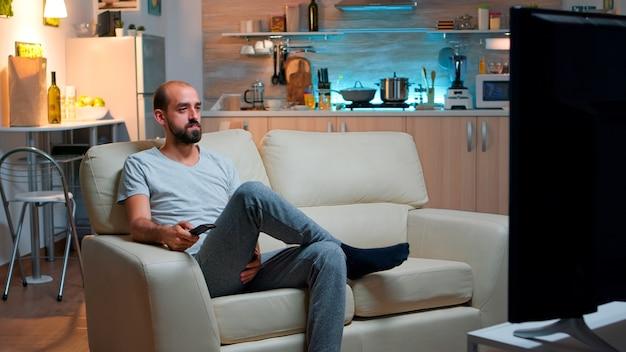 Homme concentré avec barbe regardant un film