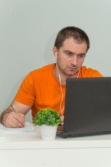 Un homme concentré en chemise orange regarde l'écran du portable, écoute la leçon en ligne et l'écriture. travail en ligne. photo verticale du concept de l'éducation en ligne