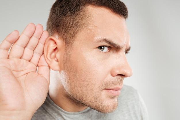 Un homme concentré essaie de vous entendre.