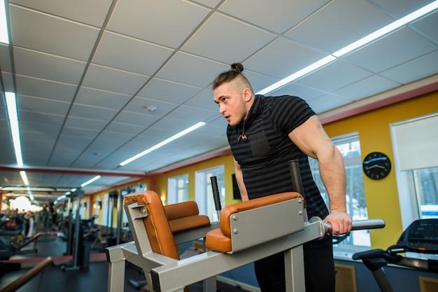 Homme concentré faisant des trempettes dans la salle de gym