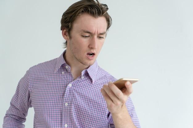 Homme concentré fronçant l'enregistrement d'un message vocal tout en utilisant un smartphone.