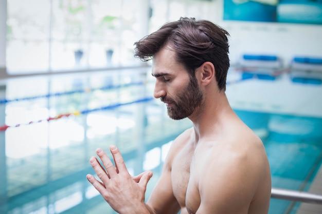 Homme concentré avec les mains ensemble à la piscine