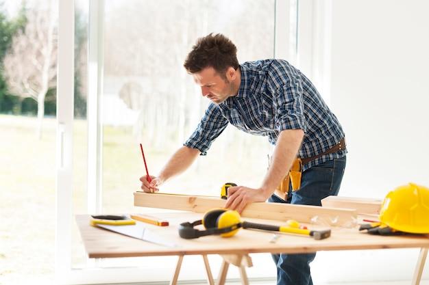 Homme concentré mesurant des planches de bois