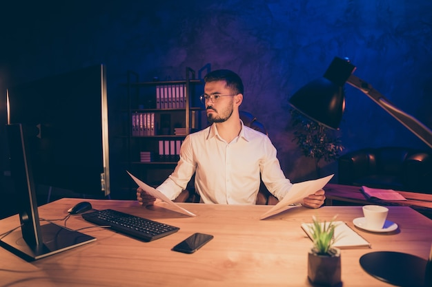 Homme concentré pensif analysant les informations sur les documents papier
