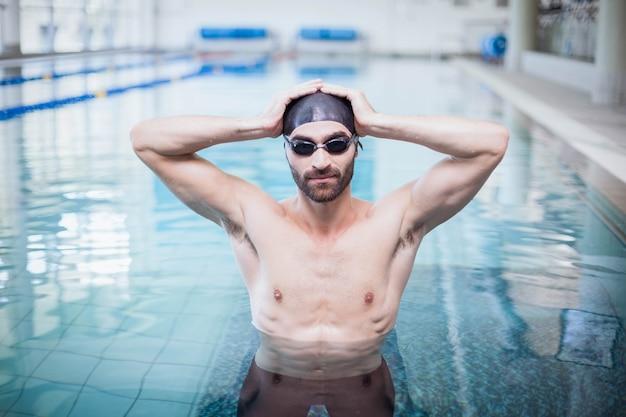 Homme concentré portant bonnet de bain et lunettes à la piscine